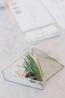 Anillos de boda en la caja triangular de cristal con arena blanca decorada con el pino en la mesa
