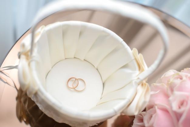 Anillos de boda en canasta blanca