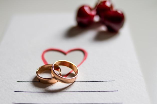 Anillos de boda y cerezas en postal blanca con corazón
