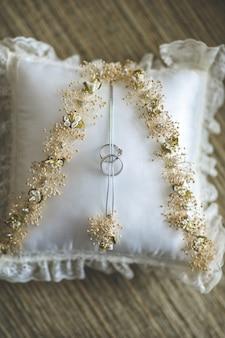 Anillos de boda cosidos al cojín tradicional listo para ser utilizado en el día de la boda.