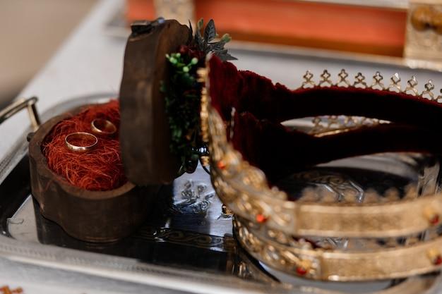 Los anillos de boda se encuentran en una caja cerca de una corona en una iglesia