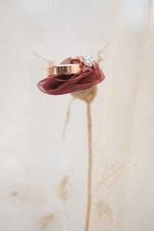 Los anillos de boda se encuentran en una rosa de tela
