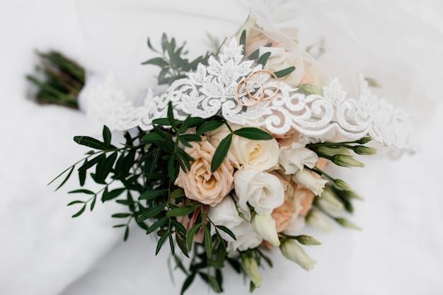 Los anillos de boda están en el velo de novia y flores.