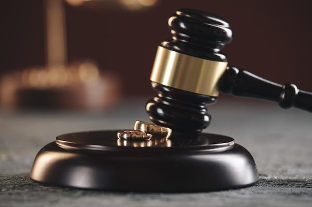 Anillos de boda en la figura de un corazón roto de un árbol, martillo de un juez sobre un fondo de madera. procedimientos de divorcio divorcio
