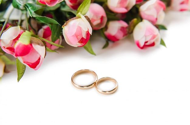 Anillos de boda y flores aisladas sobre fondo blanco