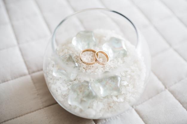 Los anillos de boda hermosos de la novia están en una taza de cristal