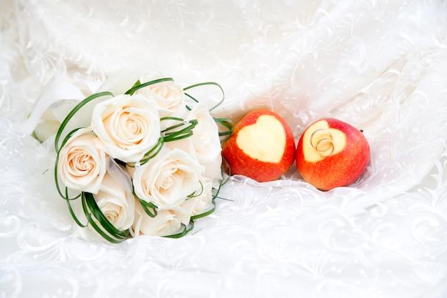 Anillos de boda en manzanas y ramo de cerca