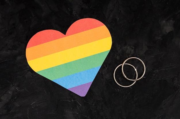 Anillos de boda multicolores y corazón lgbt sobre fondo negro