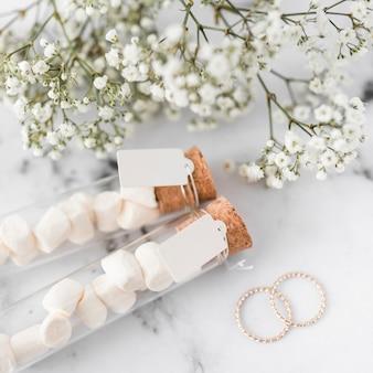 Anillos de boda de oro; aliento de bebé con flores y tubos de ensayo de malvavisco con etiqueta blanca