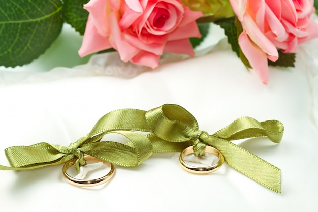 Anillos de boda de oro en la almohada blanca con rosa
