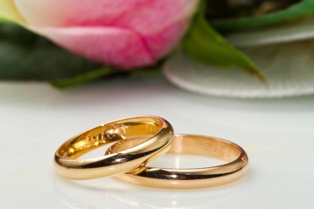 Anillos de boda y rosas rosas.