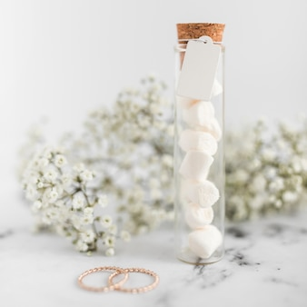 Anillos de boda; tubos de ensayo de malvavisco con etiqueta y flores de aliento de bebé sobre fondo texturizado