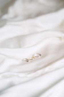 Anillos de boda vista de ángulo alto sobre un paño sobre fondo blanco.