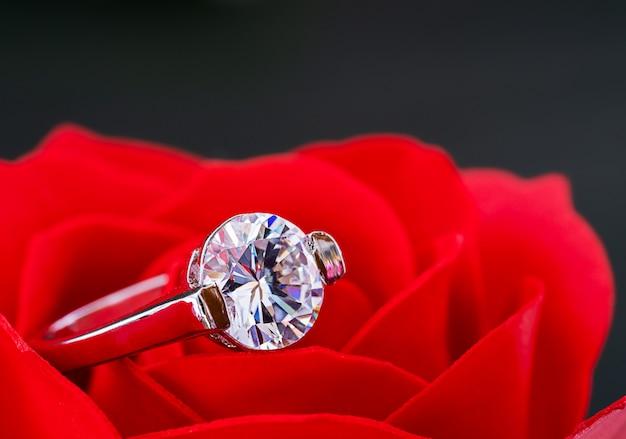 Anillos de bodas de diamantes en rosas rojas