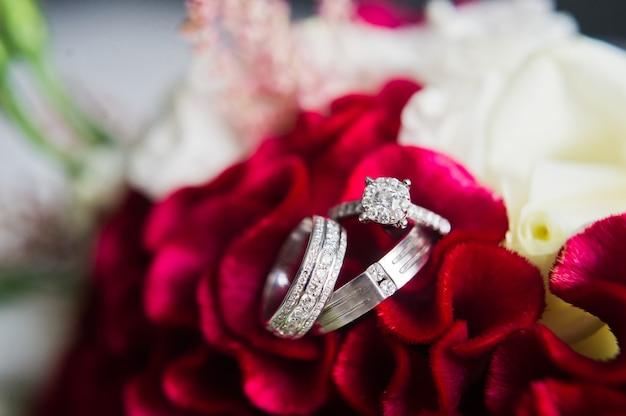 Anillos de bodas de lujo con diamantes sobre un fondo de flores, de cerca.