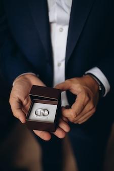 Los anillos de bodas de oro están en la mano del novio.