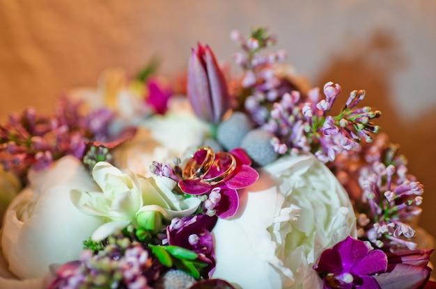 Anillos de bodas de oro sobre un fondo de flores, de cerca.