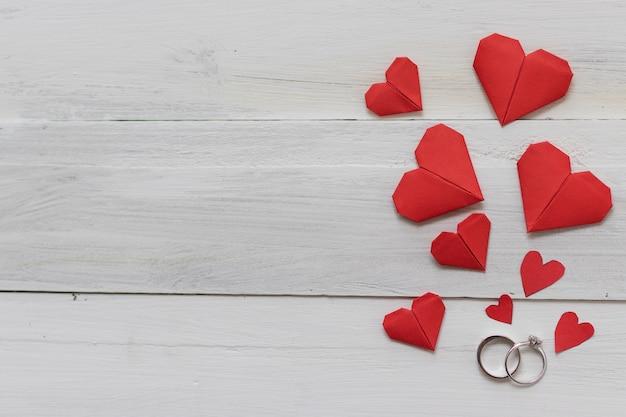 Anillos de bodas y papel de origami de corazón rojo sobre fondo blanco