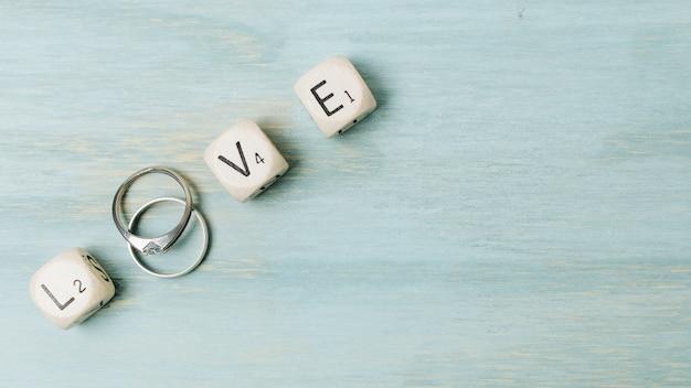 Anillos de bodas de plata con letras de amor en el escritorio de madera.