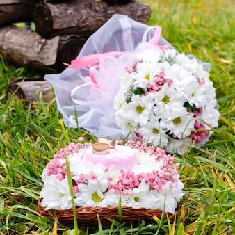Anillos de bodas en un soporte y un ramo nupcial de chamomiles blancos en una hierba verde. enfoque selectivo