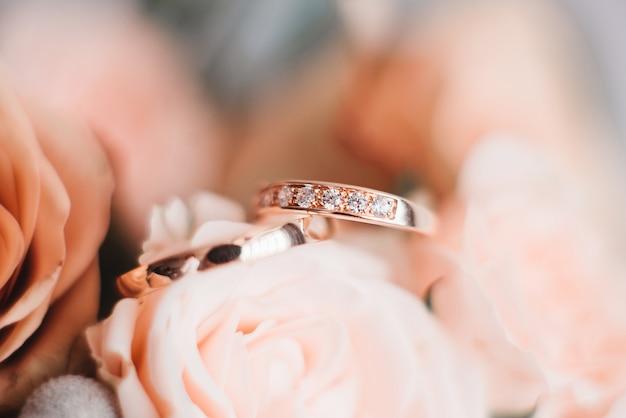 Anillos de compromiso de boda y fondo de ramo de boda de flores, enfoque selectivo, macro