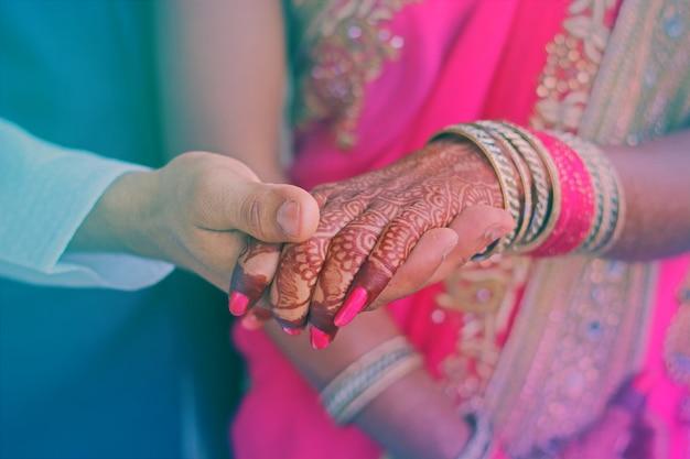 Anillos de compromiso en las manos de la novia y el novio