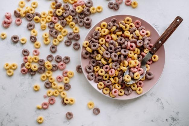 Anillos de maíz multicolores en una placa rosa para el desayuno, comida sana.