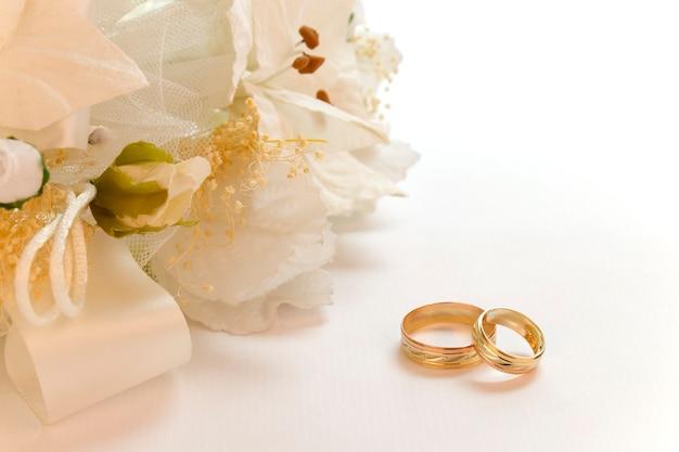 Anillos de oro para una boda romántica con flores blancas y espacio para copiar