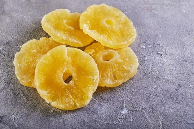 Anillos de piña confitada amarillo sobre una mesa de hormigón gris. frutos secos, tendencia de color 2021.