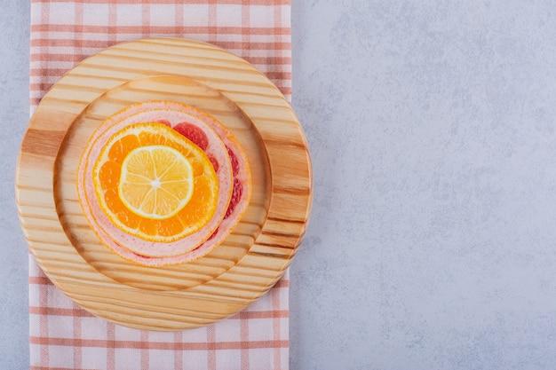 Anillos de pomelo, limón y naranja frescos en placa de madera.