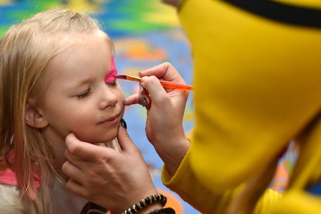 Animador pinta la cara de una niña pintando en unas vacaciones