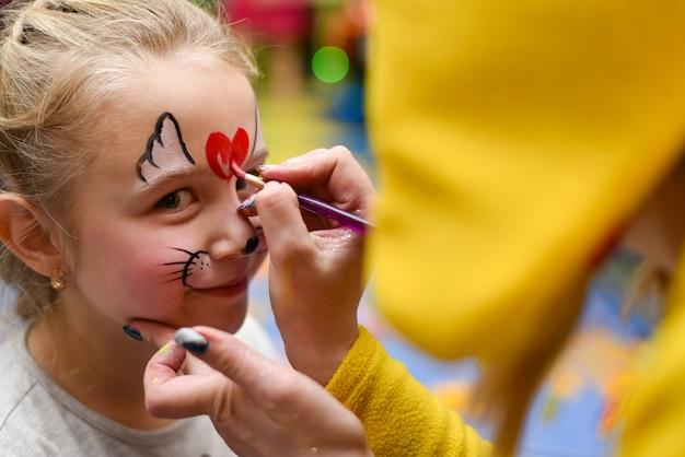 El animador pinta la cara del niño.