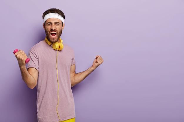 Animando al deportista feliz aprieta los puños y exclama con alegría, se regocija de sus propios logros en el deporte, levanta las manos con pesas