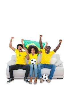 Animando fanáticos del fútbol brasileños en amarillo en el sofá