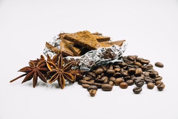 Anís estrellado; granos de café y trozos de chocolate sobre fondo blanco