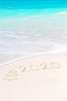 Año 2020 escrito en playa de arena blanca.