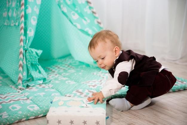 Un año alegre bebé juega en casa.