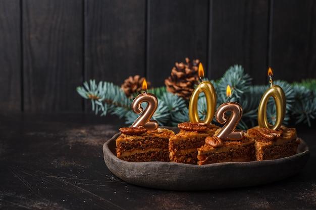 Año nuevo 2020. pastel festivo con velas en la mesa oscura, espacio de copia.