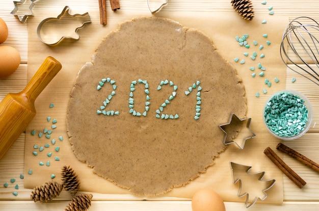 Año nuevo 2021 hecho de chispas dulces sobre masa para galletas de navidad
