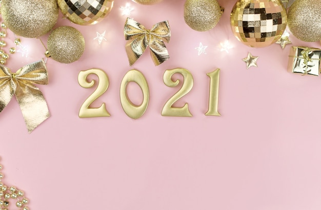 Año nuevo 2021 números dorados en el diseño de la decoración de navidad dorada en rosa.