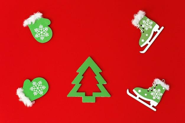 Año nuevo aplanada de juguetes de madera caseros, pequeños guantes verdes y patines, árbol de navidad sobre fondo de papel rojo. conceptos de vacaciones.