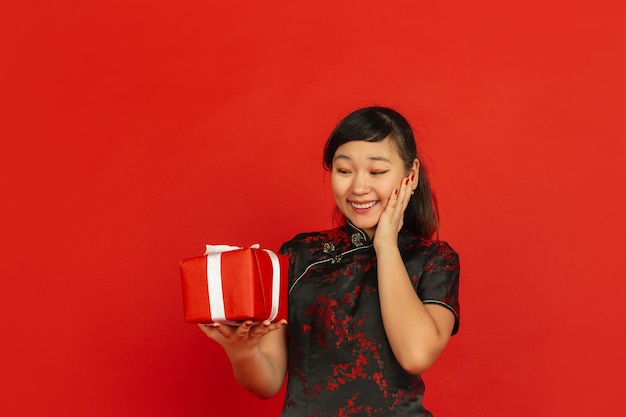 Año nuevo chino 2020. retrato de joven asiática aislado sobre fondo rojo. modelo femenino en ropa tradicional se ve feliz, sonriente y sorprendida por caja de regalo. celebración, fiesta, emociones.