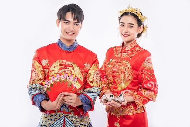 Año nuevo chino, el hombre y la mujer visten cheongsam dan dinero para regalos tradicionales