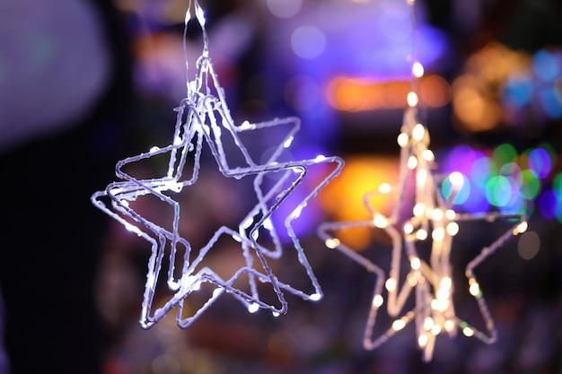 Año nuevo es guirnalda brilla en la oscuridad contra el fondo de las luces nocturnas