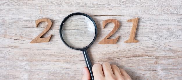 Año nuevo con mano sosteniendo lupa y número de madera