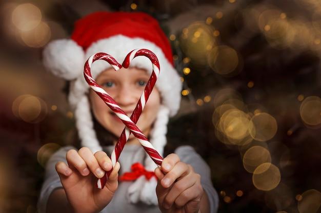 Año nuevo niña junta caramelos navideños en forma de corazón