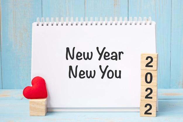 Año nuevo palabras nuevas y 2022 cubos con decoración en forma de corazón rojo sobre fondo de mesa de madera azul. concepto de objetivo, resolución, salud, amor y feliz día de san valentín