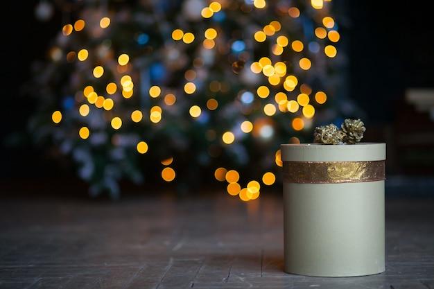Año nuevo regalo dorado festivo sobre fondo de luces de navidad
