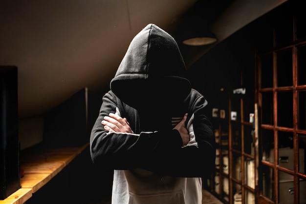 Anónimo hombre en la capucha oscura de pie en la misteriosa pose