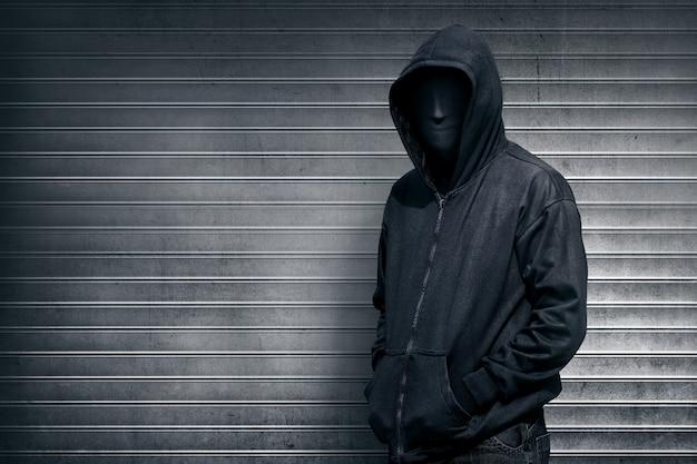 Anónimo hombre en la puerta de persiana gris